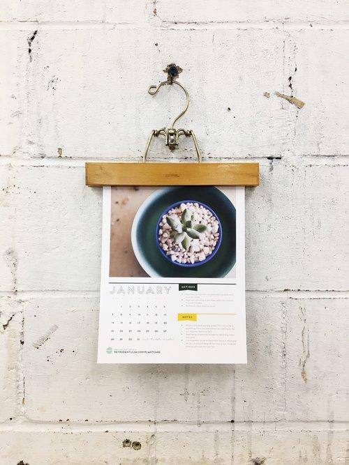calendar held by a piece of wood and brass hanger hanging on a grungy painted white cinder block wall