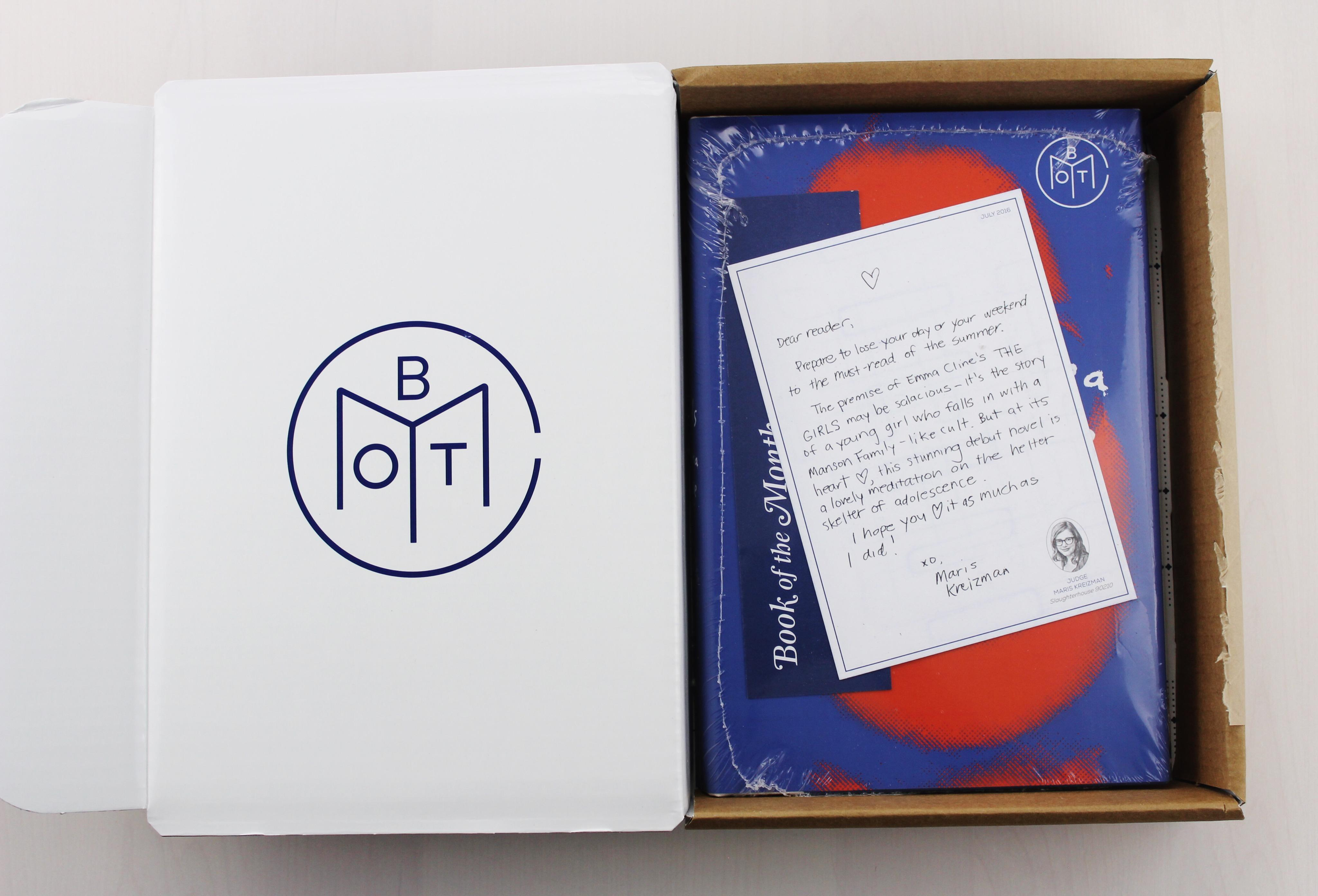 book in cellophane inside of a white box with a hand written letter atop the book