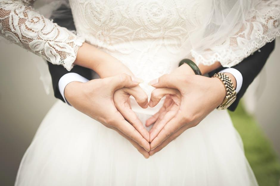 close up of a bride and grooms hands overlapping as they form the shape of a heart